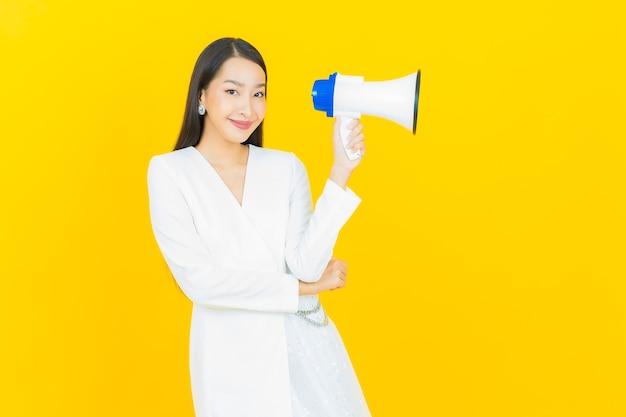 노란색 배경에 확성기와 세로 아름 다운 젊은 아시아 여자 미소
