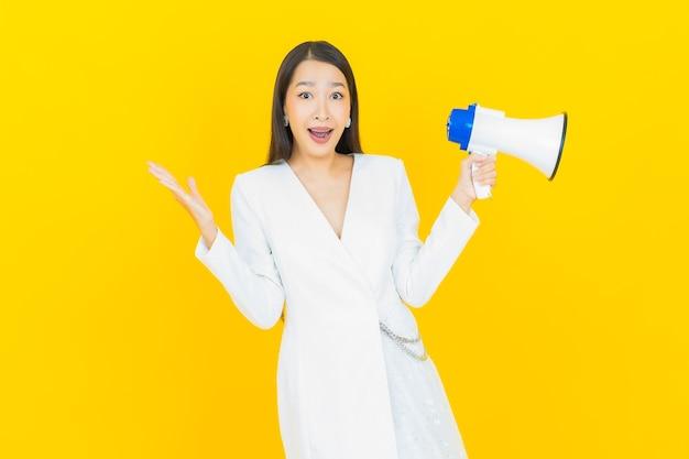 노란색 배경에 확성기와 세로 아름 다운 젊은 아시아 여자 미소 프리미엄 사진