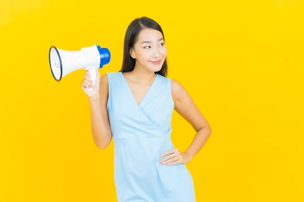 노란색 벽에 확성기와 세로 아름 다운 젊은 아시아 여자 미소