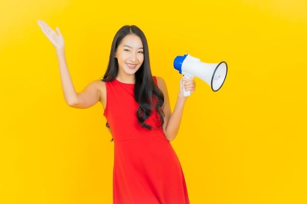 黄色の壁にメガホンで笑顔美しい若いアジアの女性の肖像画