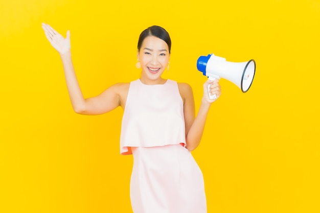 노란색에 확성기와 세로 아름 다운 젊은 아시아 여자 미소