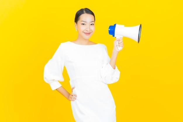 노란색에 확성기와 세로 아름 다운 젊은 아시아 여자 미소 프리미엄 사진