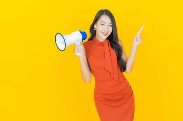 노란색에 확성기와 미소 초상화 아름 다운 젊은 아시아 여자