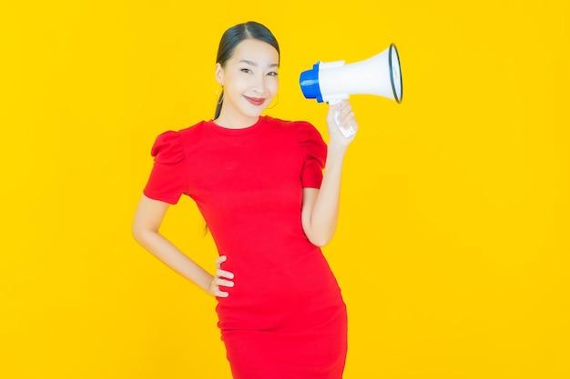 黄色のメガホンで笑顔美しい若いアジアの女性の肖像画