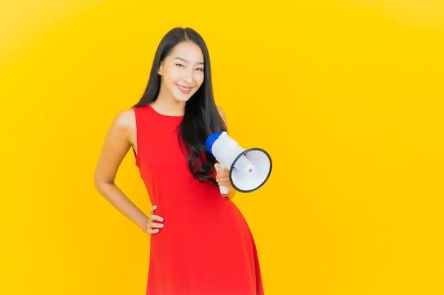 Sorriso della bella giovane donna asiatica del ritratto con il megafono sulla parete gialla