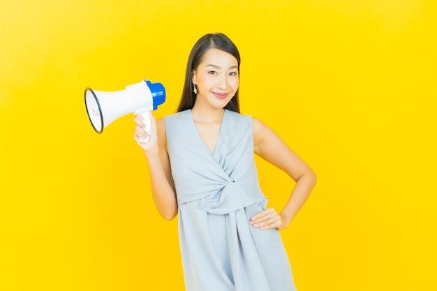 확성기와 세로 아름 다운 젊은 아시아 여자 미소