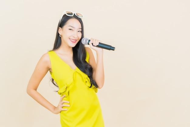 벽에 노래를위한 마이크와 세로 아름다운 젊은 아시아 여자 미소