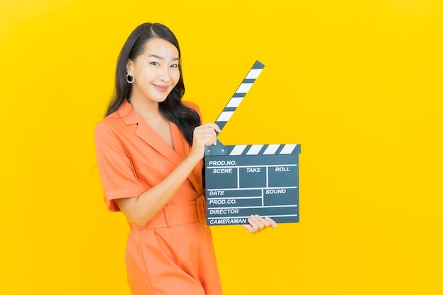 Portrait beautiful young asian woman smile with movie slate plate cutting on yellow