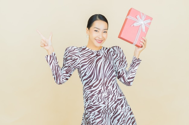 Portrait beautiful young asian woman smile with red gift box on beige