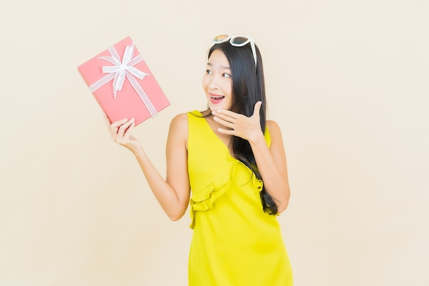 Portrait beautiful young asian woman smile with red gift box on color wall