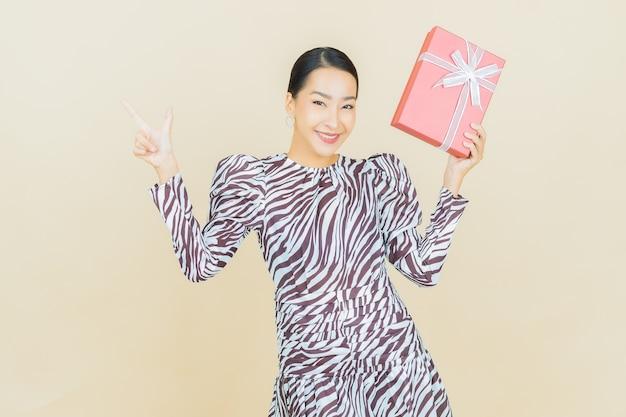 베이지 색에 빨간색 선물 상자와 세로 아름 다운 젊은 아시아 여자 미소