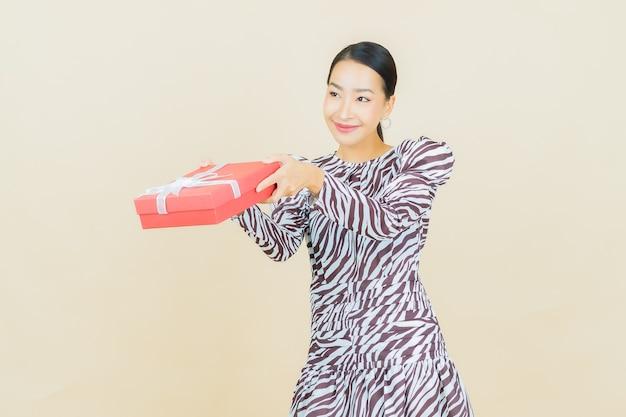 ベージュに赤いギフト ボックスで笑顔のポートレート美しい若いアジア女性