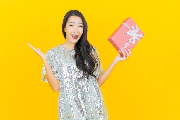 黄色の赤いギフトボックスと肖像画美しい若いアジアの女性の笑顔