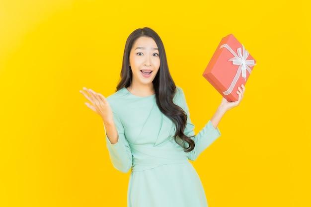 Улыбка женщины портрета красивая молодая азиатская с красной подарочной коробкой на желтом