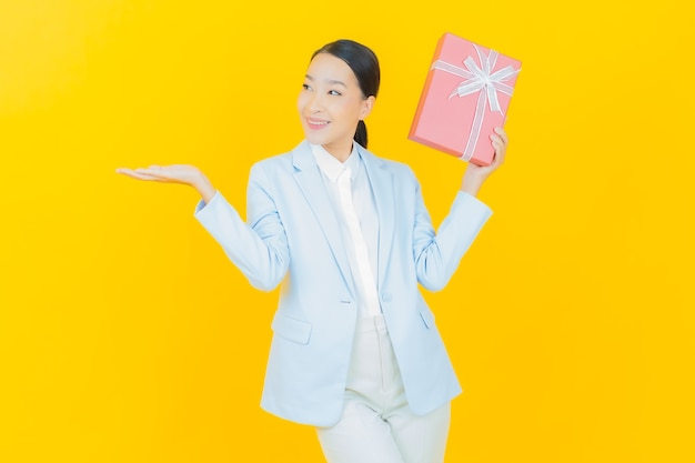 노란색에 빨간 선물 상자와 함께 초상화 아름 다운 젊은 아시아 여자 미소