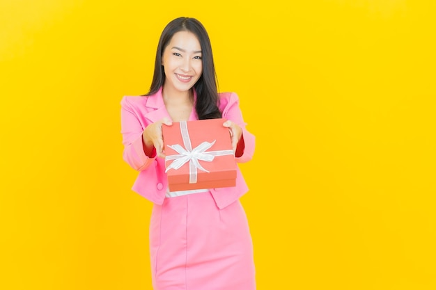 Portrait beautiful young asian woman smile with red gift box on yellow color wall