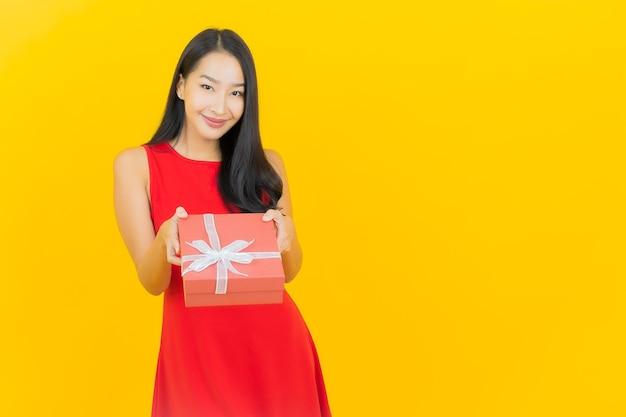 Sorriso di bella giovane donna asiatica del ritratto con confezione regalo rossa sulla parete gialla