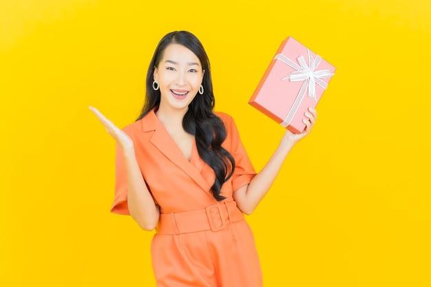 Sorriso di bella giovane donna asiatica del ritratto con confezione regalo rossa su giallo