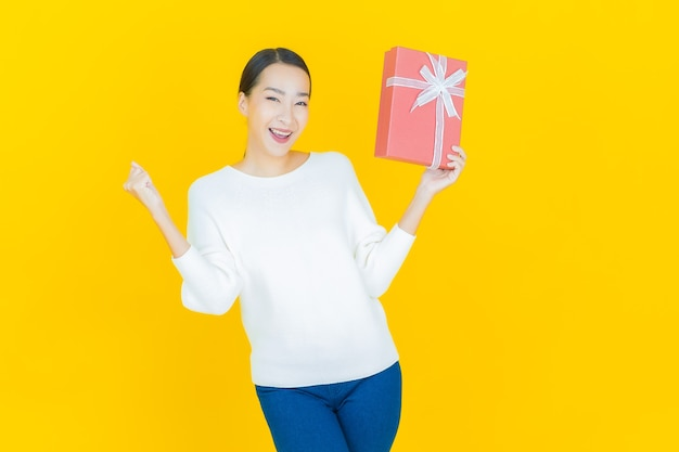 Portrait beautiful young asian woman smile with red gift box on yellow