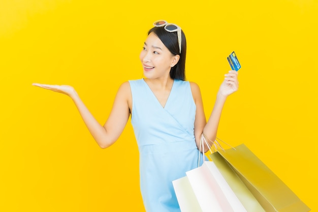 Улыбка женщины портрета красивая молодая азиатская с хозяйственной сумкой на стене желтого цвета