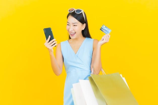 黄色の壁に買い物袋と肖像画美しい若いアジアの女性の笑顔