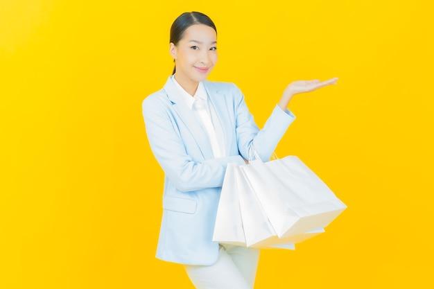 노란색에 쇼핑백을 들고 웃는 아름다운 젊은 아시아 여성 초상화