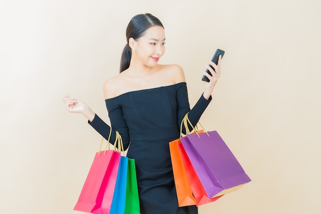 Sorriso di bella giovane donna asiatica del ritratto con la borsa della spesa su yellow