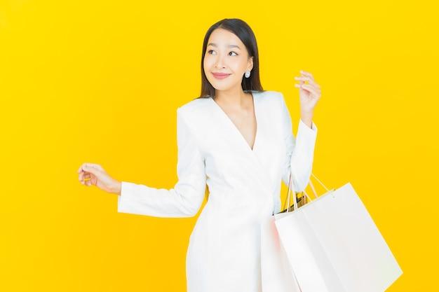 肖像画の美しい若いアジアの女性が買い物袋で笑顔
