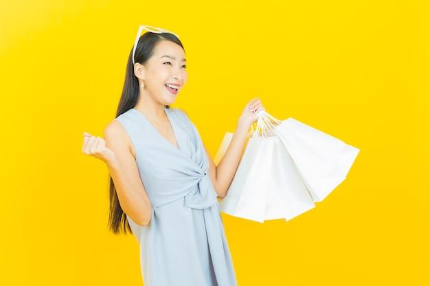 Улыбка женщины портрета красивая молодая азиатская с хозяйственной сумкой
