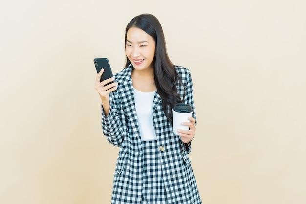 Sorriso di bella giovane donna asiatica del ritratto con il telefono cellulare astuto su beige