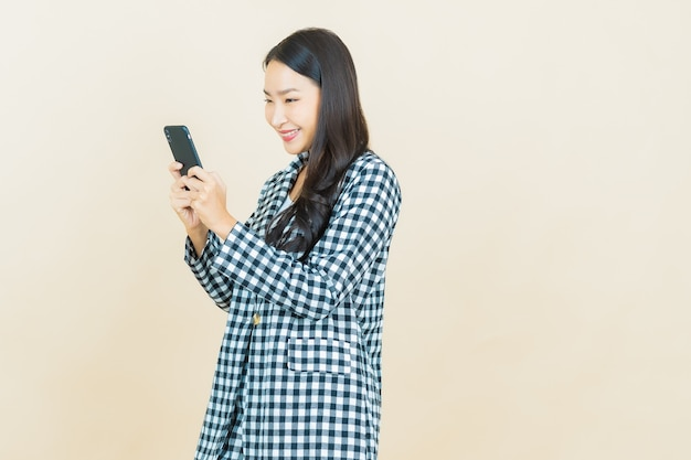 Portrait beautiful young asian woman smile with smart mobile phone on beige