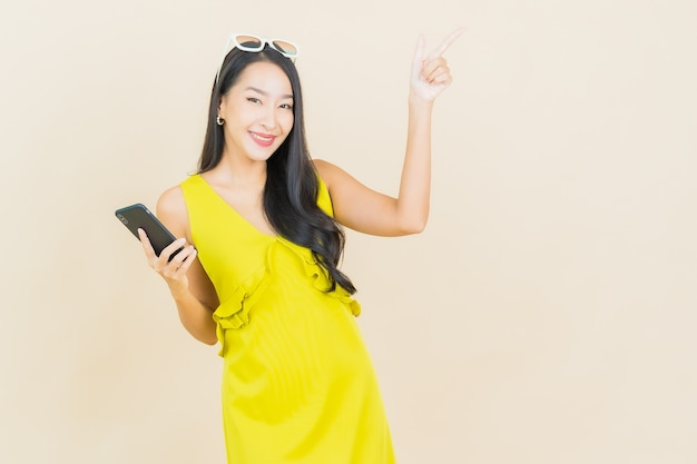 Portrait beautiful young asian woman smile with smart mobile phone on color wall