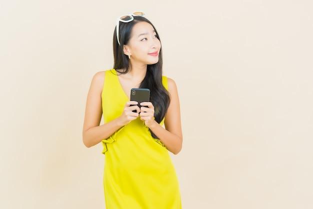 色の壁にスマート携帯電話で笑顔美しい若いアジアの女性