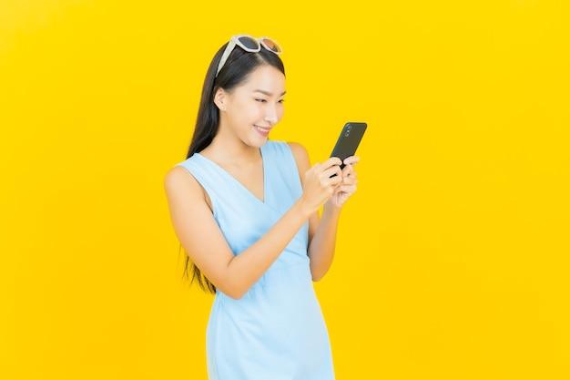 Улыбка женщины портрета красивая молодая азиатская с умным мобильным телефоном на стене желтого цвета