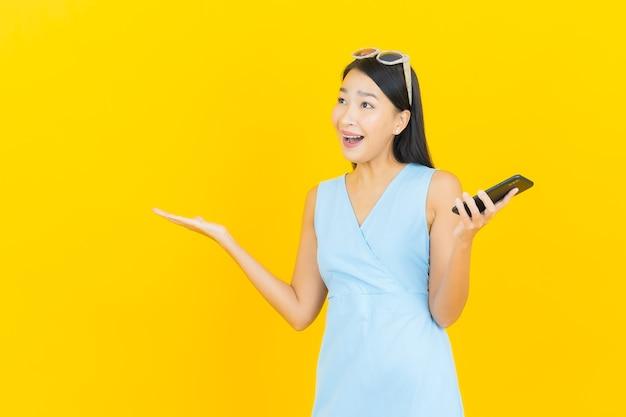 黄色の壁にスマートな携帯電話で笑顔美しい若いアジアの女性の肖像画