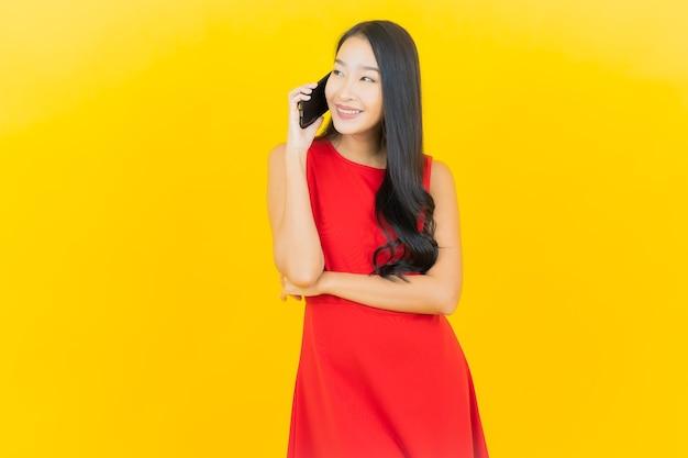 Улыбка женщины портрета красивая молодая азиатская с умным мобильным телефоном на желтой стене