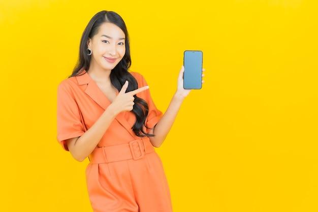 노란색에 스마트 휴대 전화와 초상화 아름 다운 젊은 아시아 여자 미소
