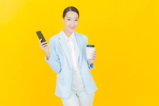 노란색에 스마트 휴대 전화와 함께 초상화 아름 다운 젊은 아시아 여자 미소