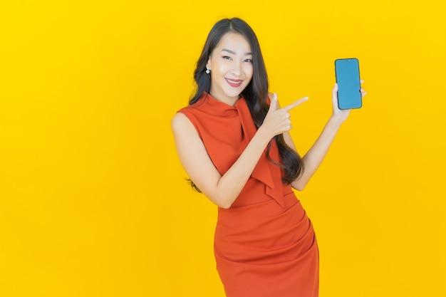 黄色のスマート携帯電話で笑顔美しい若いアジアの女性の肖像画