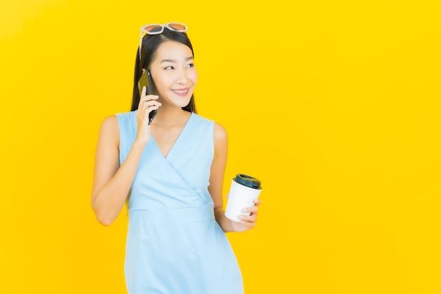 Sorriso della bella giovane donna asiatica del ritratto con il telefono cellulare astuto sulla parete di colore giallo
