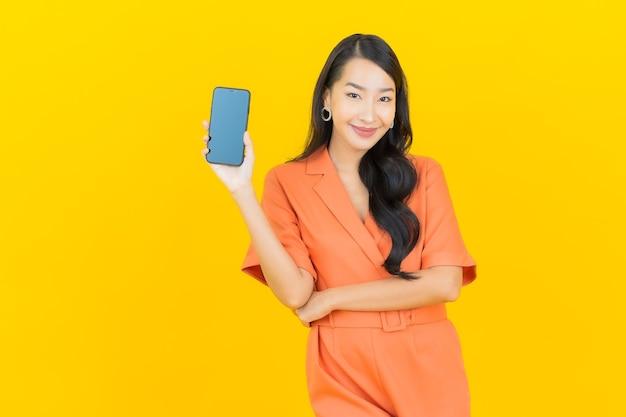 Ritratto bello giovane sorriso asiatico della donna con il telefono cellulare astuto su colore giallo