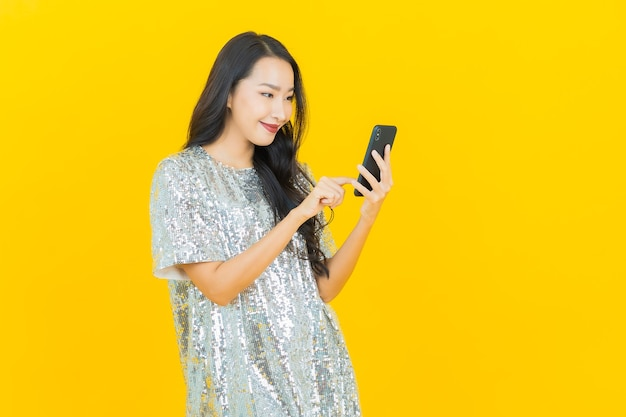 Portrait beautiful young asian woman smile with smart mobile phone on yellow