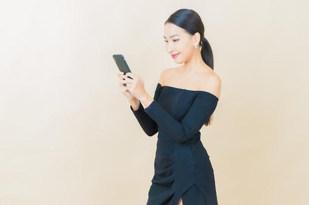 Sorriso di bella giovane donna asiatica del ritratto con il telefono cellulare astuto su yellow