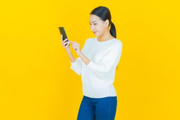 Ritratto di una bella giovane donna asiatica che sorride con un telefono cellulare intelligente su giallo