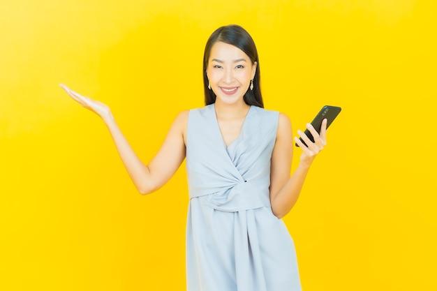 Улыбка женщины портрета красивая молодая азиатская с умным мобильным телефоном