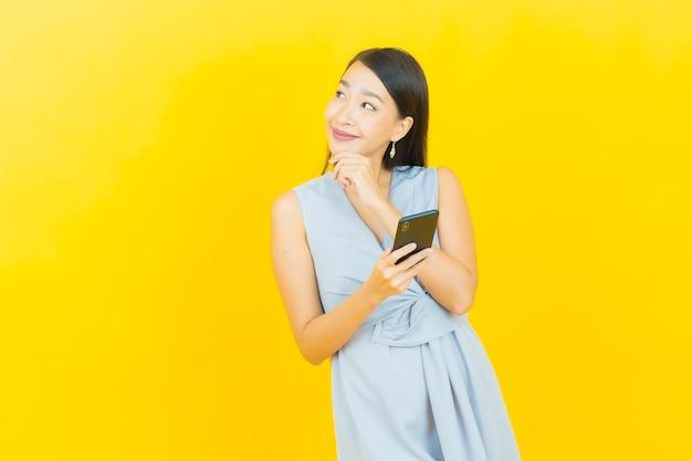 肖像画美しい若いアジアの女性がスマートな携帯電話で笑顔