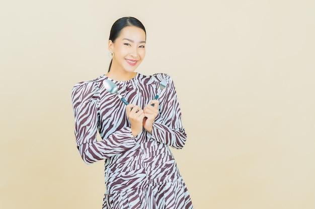 ベージュのスプーンとフォークで笑顔のポートレート美しい若いアジア女性