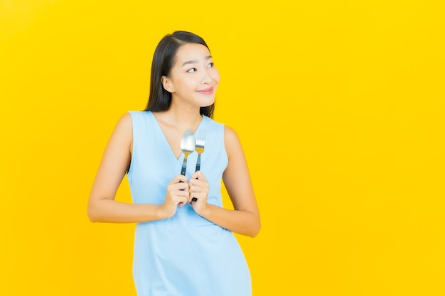 黄色の色の壁にスプーンとフォークで笑顔美しい若いアジアの女性の肖像画