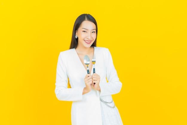 肖像画美しい若いアジアの女性はスプーンとフォークで笑顔