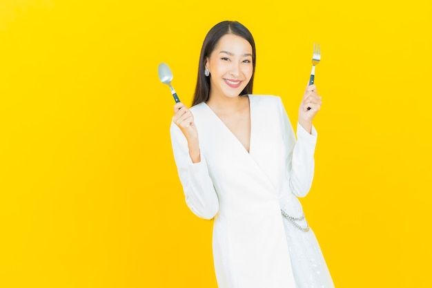Portrait beautiful young asian woman smile with spoon and fork